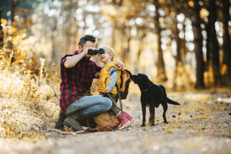 Vater mit Kind und Hund stehen im Wald und schauen durch ein Fernglas